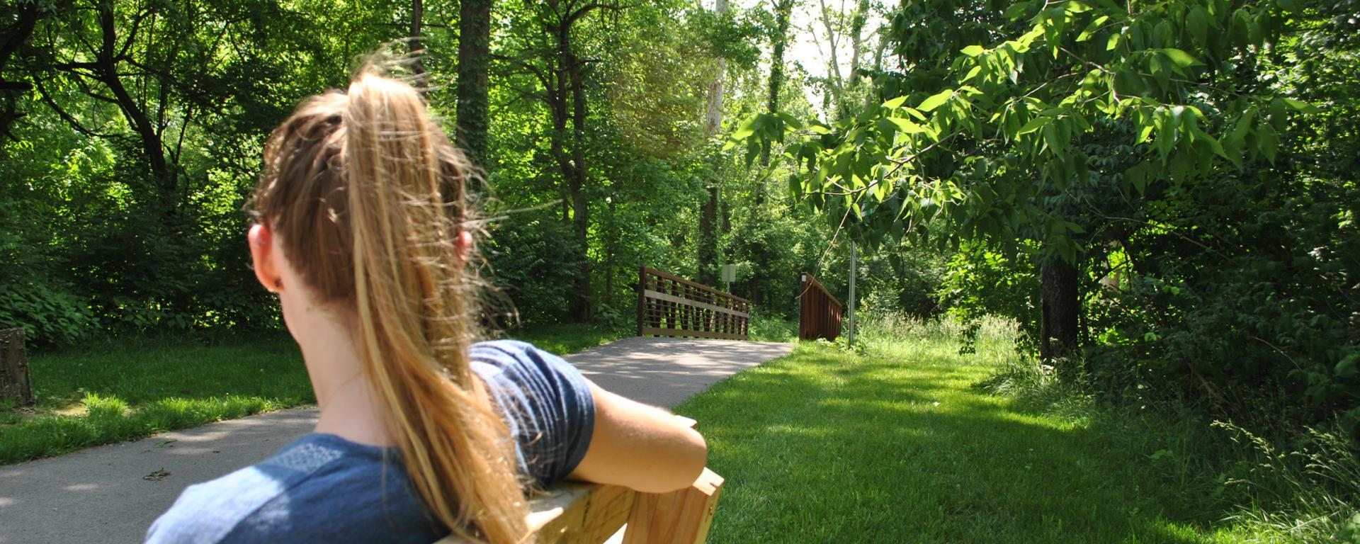 girl on bench by park trail